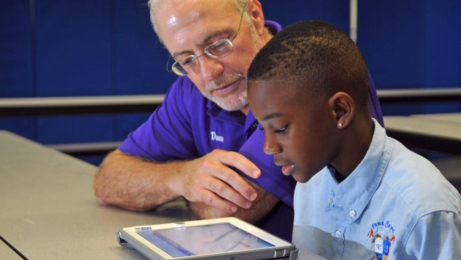 Dave Brown, with United Way and Rolling Readers, mentors 3rd grader Vahreion Krikman, age 9. United Way of Brevard has teamed up with Emma Jewel Charter Academy in Cocoa to provide the MyON electronic books program.