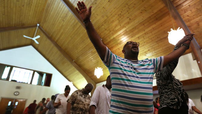 The Rev. Kevin Mallory joins in a worship song during a vigil in Indianapolis for victims of Wednesday night's church shooting in Charleston, S.C. Thursday's vigil was held at St. John African Methodist Episcopal Church.