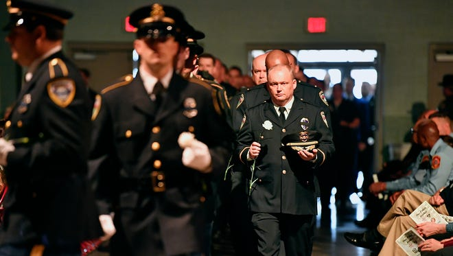 Interim York City Police Chief Troy Bankert carries a white carnation as he enters the memorial service for Officer Alex Sable on Friday. Police from all over the county, state and nearby states attended.
