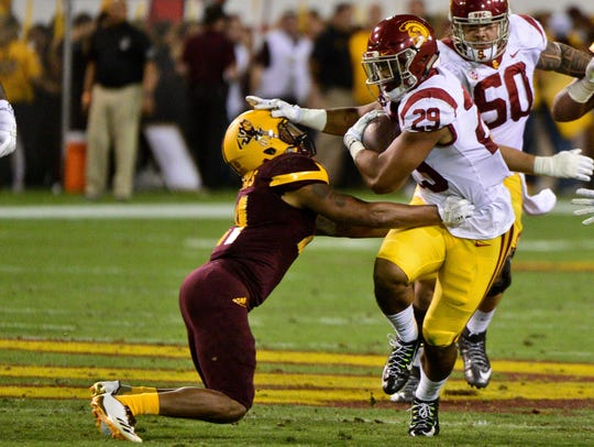 USC running back Vavae Malepeai (right) stiff arms ASU defensive back Chad Adams during the first half on Saturday.