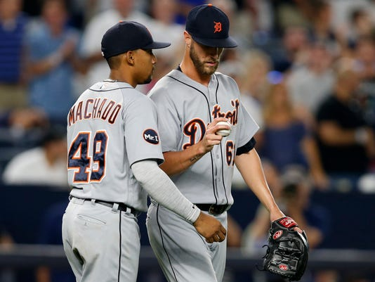 Detroit Tigers shortstop Dixon Machado (49) talks to relief pitcher Shane Greene (61) after Greene threw the ball past first base on a pickoff attempt, allowing New York Yankees' Jacoby Ellsbury to advance to third during the ninth inning of a baseball game at Yankee Stadium in New York, Tuesday, Aug. 1, 2017. Greene earned the save when Clint Frazier popped out to Machado to end the game. (AP Photo/Kathy Willens)