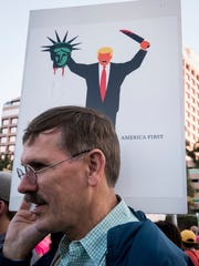 A man protests in front of Trump Plaza holding a sign depicting the cover of the German magazine Der Spiegel in West Palm Beach, Fla. as President Donald Trump and first lady Melania attend the 60th annual Red Cross Ball at Trump's Mar-a-Lago resort on Saturday, Feb. 4, 2017.