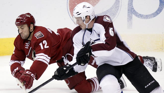 Phoenix Coyotes left winger Paul Bissonnette, left, and Colorado Avalanche defenseman Erik Johnson, right, compete for the puck in the third period of an April 6, 2013, game in Glendale, Ariz.