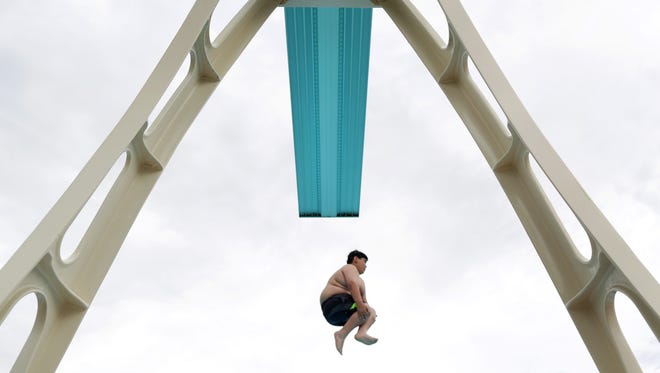 Yacine Bentaalla does a cannon ball off of the high dive Friday during opening day at Mead Pool in Appleton.