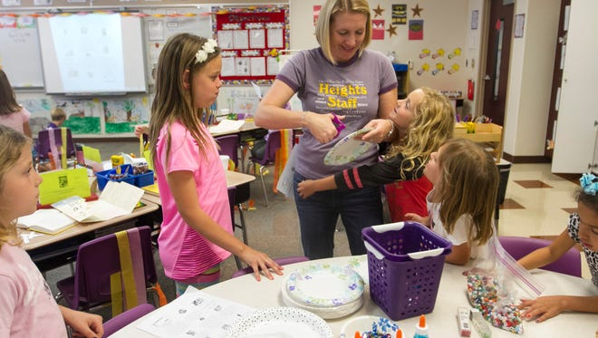Second-grade teacher Monica Nelson helps her students on Thursday at Heights Elementary School. Nelson was one of the 2016 Golden Apple winners.