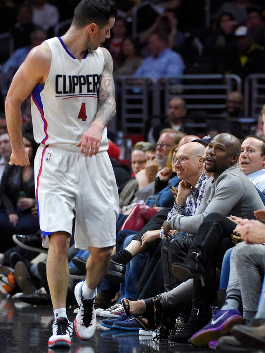 Floyd Mayweather, Jr., right, talks to Los Angeles Clippers guard J.J. Redick during the second half of an NBA basketball game against the Phoenix Suns, Monday, Feb. 22, 2016, in  Los Angeles. The Clippers won 124-84. (AP Photo/Mark J. Terrill)
