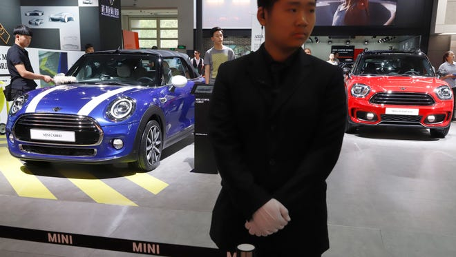 A security guard stands near MINI cars displayed at the China Auto Show in Beijing. BMW Group and China's biggest SUV brand, Great Wall Motor, announced Tuesday, July 10, 2018, a partnership to produce electric MINI vehicles in China.