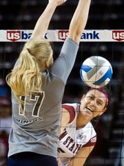 New Mexico State's Andrea Tauai hits around the outstretched arms of UTEP's Ashley Grzenbeniak during the first set Tuesday night at the Pan American Center.