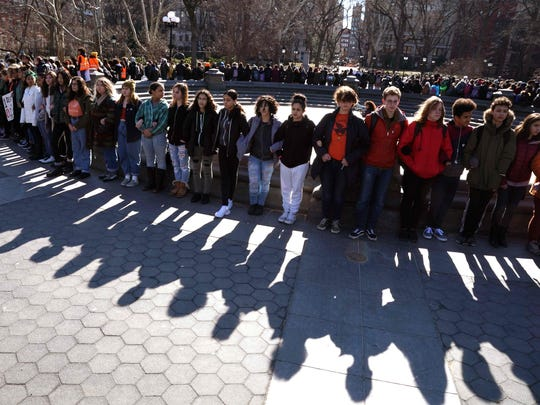 Students from Harvest Collegiate High School form a circle around the fountain in Washington Square Park on March 14, 2018 in New York to take part in a national walkout to protest gun violence.