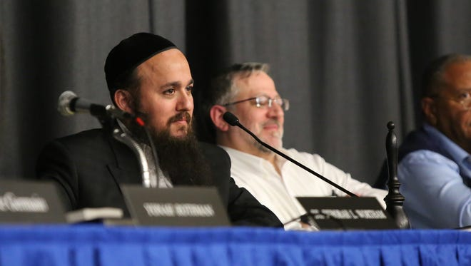 East Ramapo School Board President Yehuda Weissmandl, left, looks to the room of attendees during a school board meeting at East Ramapo High School on Tuesday, Dec. 15, 2015.