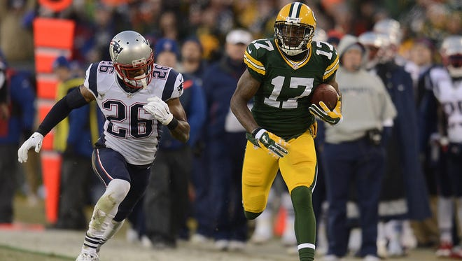 Green Bay Packers receiver Davante Adams (17) runs away from New England Patriots cornerback Logan Ryan (26) after making a catch during Sunday's game at Lambeau Field.