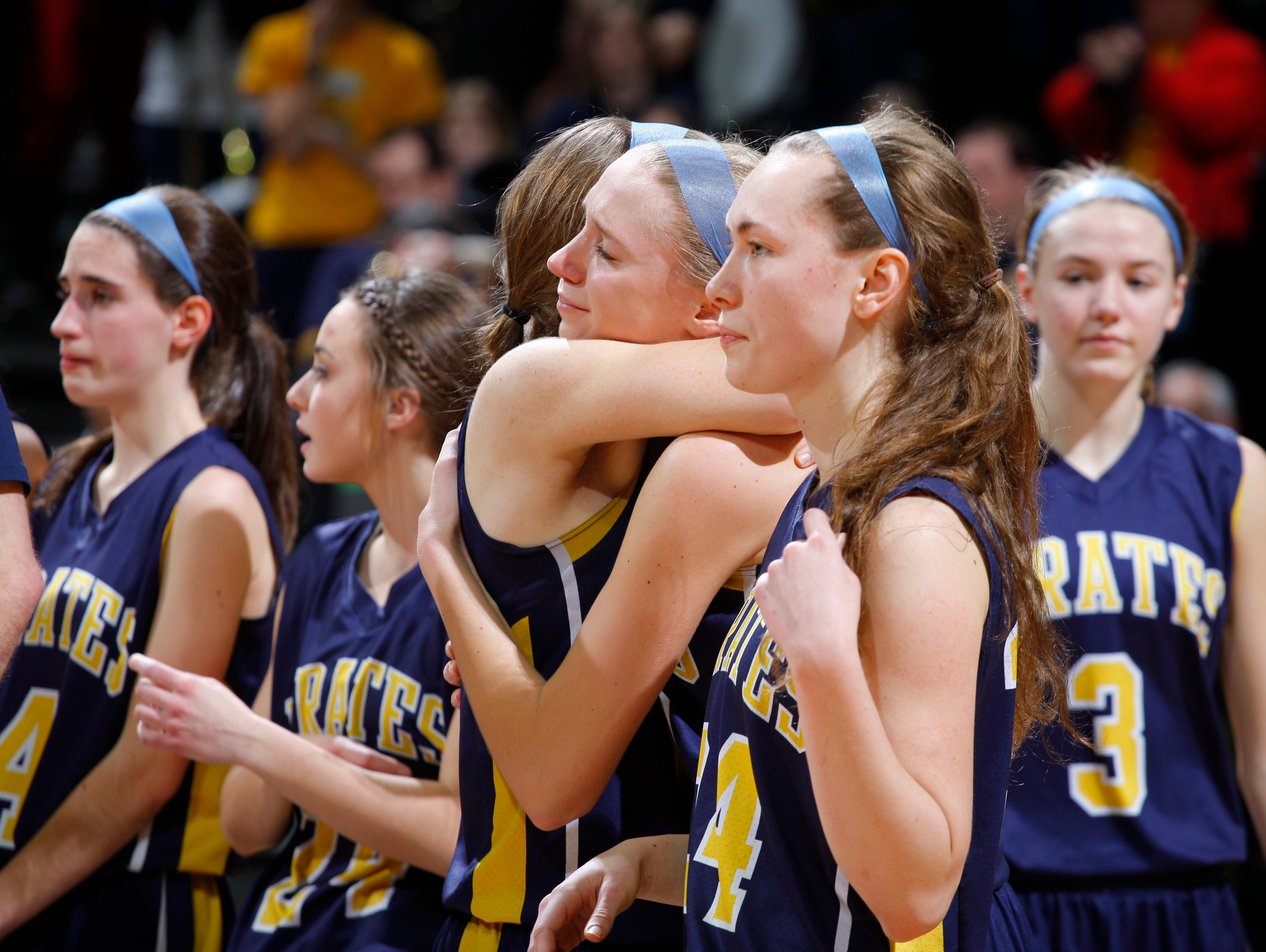 Pewamo-Westphalia's Emily Spitzley, center facing, and Kenzie Hengesbach hug as Rachel Huhn, from left, Olivia Nurenberg, Kate Hengesbach and Hannah Spitzley (3) react following their 46-44 loss to Detroit Edison their MHSAA Class C championship game, Saturday, March 18, 2017, in East Lansing, Mich.