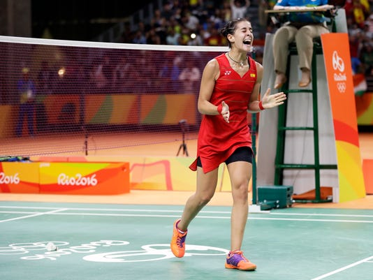Spain's Carolina Marin celebrates after defeating India's V. Sindhu Pusarla in the women's badminton singles gold medal match at the 2016 Summer Olympics in Rio de Janeiro, Brazil, Friday, Aug. 19, 2016. (AP Photo/Kin Cheung)