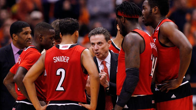 Louisville head coach Rick Pitino, center, talks to his players during a time out in the final seconds of an NCAA college basketball game against Syracuse in Syracuse, N.Y., Wednesday, Feb. 18, 2015. Syracuse won 69-59. (AP Photo/Nick Lisi)