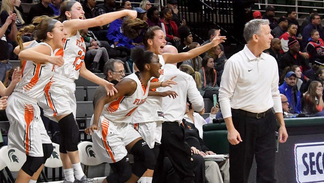 Flushing players come off the bench in joy as the final buzzer sounds and Flushing beats East Kentwood, 49-38, in their MHSAA Class A Championship.