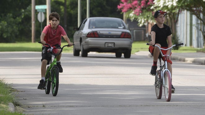 A pair of young men make their way along Cornwell Ave on their bicycles after passing a motorist.