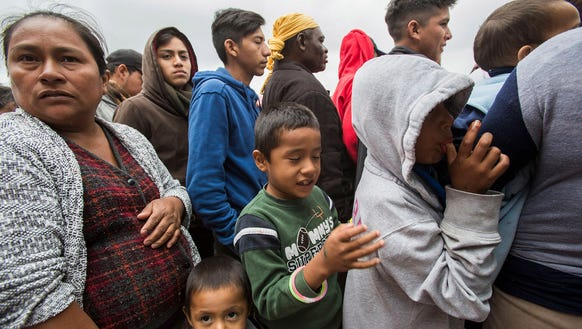 Central American migrants line up to get food at their