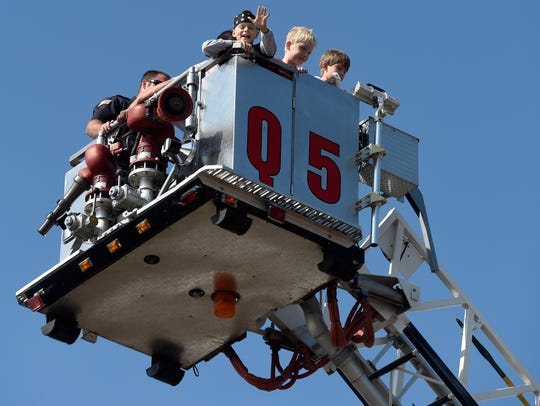 "Elijah Barber, 9, of Evansville waves as he says ""hello everyone down there"" while going for a ride on the McCutchanville Fire Department's quint 5 ladder truck along with William Rogers, 9, and Jamison Voyles, 9, of Newburgh during a past Trucks and Heroes event at Deaconess Gateway Hospital in Newburgh."