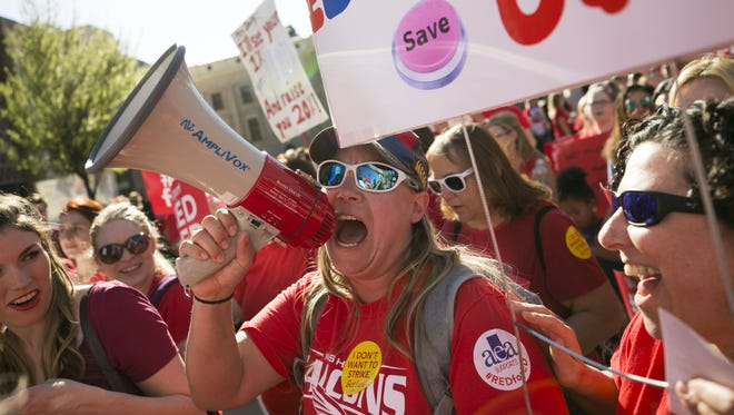 Lindsay Breon, a physical education teacher at Washington Elementary School in Phoenix, shouts into a megaphone while  rallying to support teachers during a #RedForEd rally at the Arizona State Capitol in Phoenix on March 28, 2018.