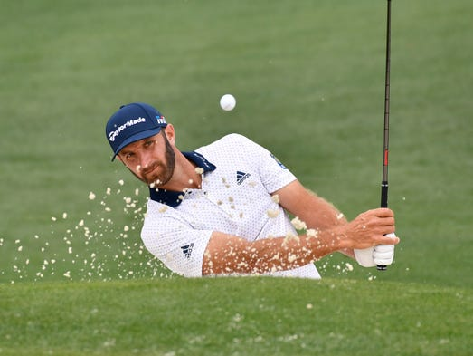 Dustin Johnson hits out of a bunker on the 2nd hole