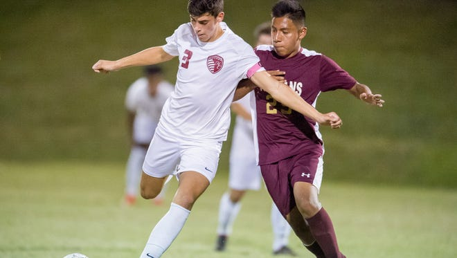 Henderson County's Brett Royster (3) and Webster County's Michael Velazquez (25) battle for the ball during the Sixth District championship game at Union County High School in Morganfield,  Tuesday, Oct. 11, 2016.