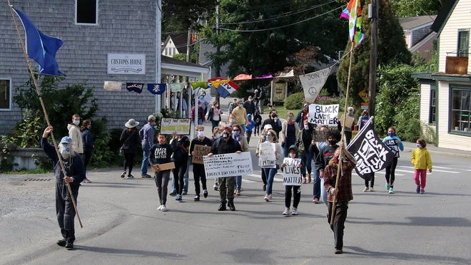 Protesters carry signs as they walk down Commercial Street in Wellfleet during a Black Lives Matter march and rally Sunday afternoon.