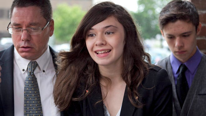 In this June 12, 2013, file photo, transgender student Nicole Maines, center, with her father Wayne Maines, left, and brother Jonas, speaks to reporters outside the Penobscot Judicial Center in Bangor, Maine.