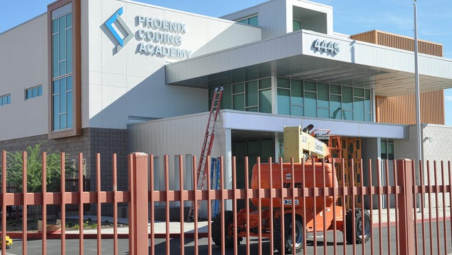 Workers put up the new sign for Phoenix Union High School District's newest school, Phoenix Coding Academy. The school will start with a freshman class of 120, eventually growing to roughly 400 students overall.