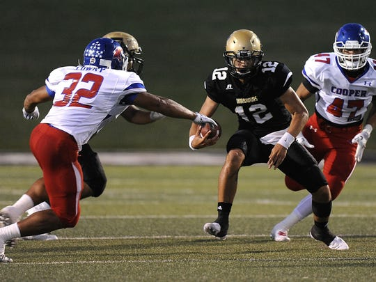 Abilene High quarterback Peyton Killam (12) cuts past Cooper linebacker Actavias Lowry (32) during the first quarter of the Eagles' 55-38 win in the crosstown football game Sept. 9 at Shotwell Stadium.