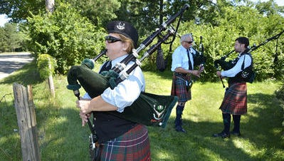 Mitzi VanderHarst, of Troy, warms up before the massed pipe bands march in this 2013 file photo. She plays with the Cabar Feidh Pipe Band, based in Royal Oak. Behind her are band members Ed Nettle of Plymouth and Paul McLeod of Royal Oak. The Highland Games return to Livonia this weekend.