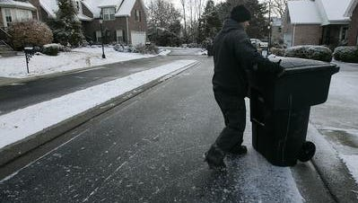 This file photo from Jan. 11, 2011, shows a Murfreesboro Solid Waste Department worker sliding across an icy street to return a garbage can in a subdivision on Haynes Drive.