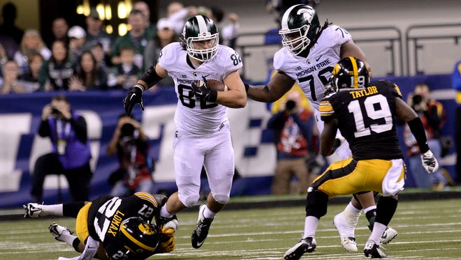Donavon Clark (76) provides a block as MSU tight end Josiah Price gets tripped up by an Iowa defender December, 5, 2015, in Indianapolis during MSU's 16-13 win over Iowa in the Big Ten Championship football game.