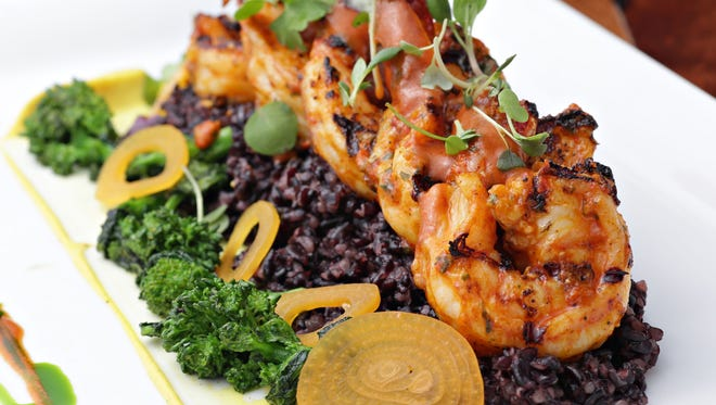 The grilled piquillo pesto shrimp over rice over black rice.