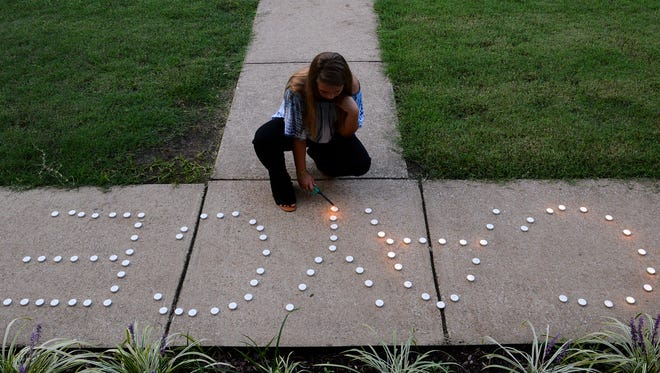 McKenzie Gross lights candles that spell out Cayce during a vigil, Thursday, Aug. 16, held for missing Milan woman Cayce McDaniel who was reported missing 22 years ago.
