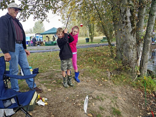 Alex Ricker, 8, helps his sister, Ciara, 10, land a trout while fishing at St. Louis Ponds with their grandfather, Joe Ricker of Salem during a youth fishing event held by the Oregon Department of Fish and Wildlife in 2014.