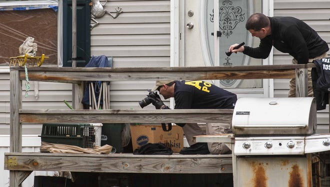Investigators search a home in Berlin on Wednesday, December 16, 2015, where suspects were arrested in connection with a fatal fire in Northfield.