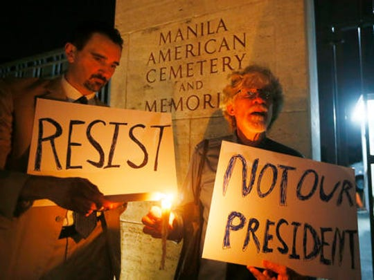 American residents in the Philippines Gabriel Ortiz, left, and Donald Goertzen display placards during a candlelight vigil at the American Cemetery to protest the inauguration of President-elect Donald Trump as the 45th President of the United States Friday, Jan. 20, 2017 in suburban Taguig city east of Manila, Philippines.