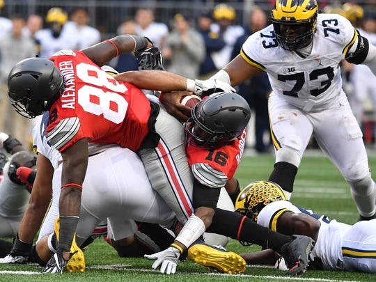 Ohio State's J.T. Barrett rushes for a first down in double overtime against Michigan at Ohio Stadium on Nov. 26, 2016.