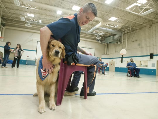 Lloyd Farr works with Kody, a golden retriever. The Prison Puppies initiative benefits both the inmates and the Leader Dog program.