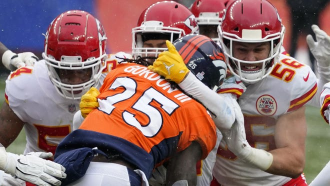 Denver Broncos running back Melvin Gordon (25) is brought down by Kansas City Chiefs linebacker Ben Niemann (56) and others during the first half of Sunday's game in Denver.