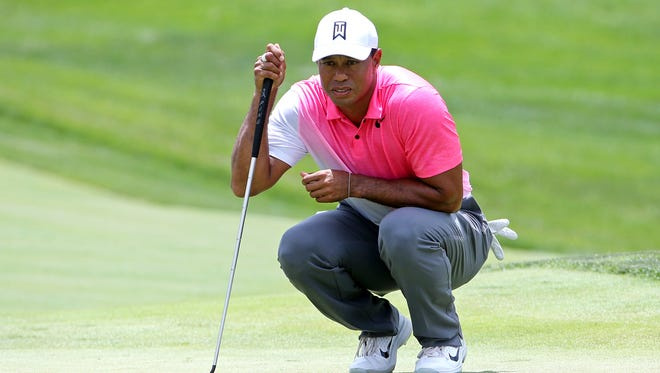 Tiger Woods lines up his putt on the first green during the first round of the Quicken Loans National golf tournament at TPC Potomac at Avenel Farm.