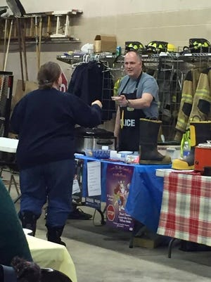 Unadilla Police Sgt. Mike Matich hands a bowl of his hot chili to a customer at a contest sponsored by the township Fire Department.