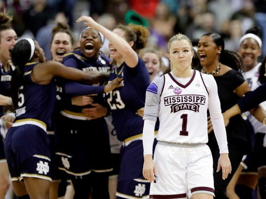 Notre Dame's Arike Ogunbowale is congratulated by teammates as Mississippi State's Blair Schaefer (1) walks away after Ogunbowale made a 3-point basket to defeat Mississippi State 61-58 in the final of the women's NCAA Final Four college basketball tournament, Sunday, April 1, 2018, in Columbus, Ohio. (AP Photo/Tony Dejak)