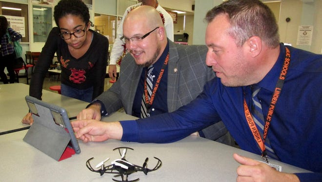 McManus Middle School eighth-grader Isabelle Brito working with Superintendent Danny A. Robertozzi and Director of Technology Michael Walters on coding to make their drone fly.