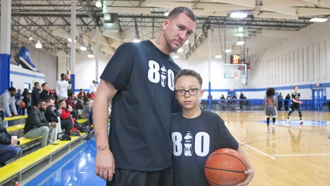 """Chris McLavish Sr. and his son Chris Jr. of the Flint Town Elite Runnin' Rebels sport their 810 shirts. 810  is the area code for Flint, Mich. The image of a bottle of water stands in for the """"1."""" Flint has suffered a four-year water crisis caused by lead leaching into tap water."""