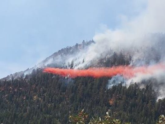 An airplane drops retardant on the Oak Grove Fire
