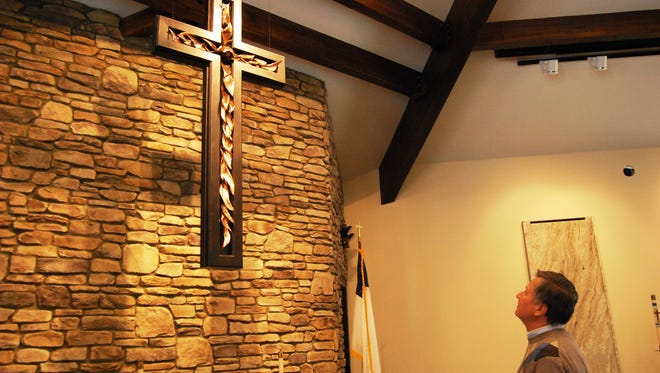 The Rev. Alan Schwieger looks at a large crucifix made of wood and hammered copper inside the new sanctuary at Immanuel Lutheran Church in St. Clair.