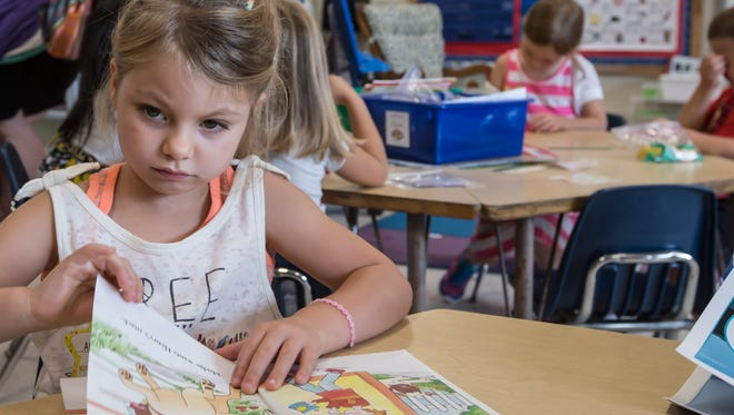 Aleigha Akins browses through books in a kindergarten class at Washington Elementary on the first day of school.