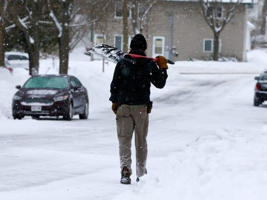 A person walks with his shovel Monday, April 16, 2018,