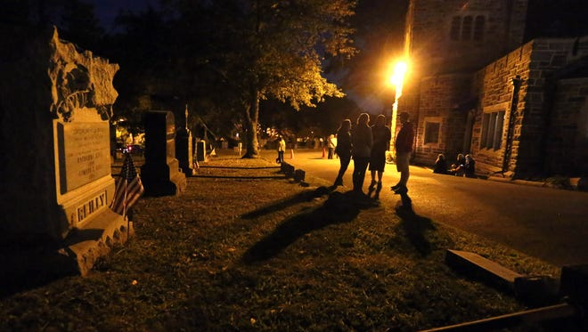 """People gather in front of the chapel/office as they wait for a nighttime lantern tour called """"Murder and Mayhem"""" to begin at the Sleepy Hollow Cemetery, Sept. 26, 2015."""